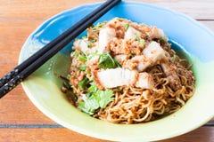 Spicy stir fried noodles. With crispy pork and chopstick stock photo