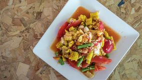 Spicy sweet corn salad. With salted egg in white plate over wooden background ,Thai style food royalty free stock photo