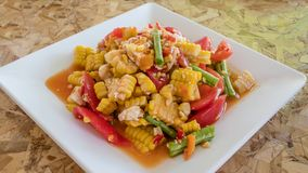 Spicy sweet corn salad. With salted egg in white plate over wooden background ,Thai style food royalty free stock photography