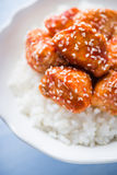 Spicy sweet and sour chicken with sesame and rice on blue wooden background. Oriental food Royalty Free Stock Photos