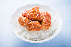 Spicy sweet and sour chicken with sesame and rice on blue wooden background. Oriental food Stock Photo