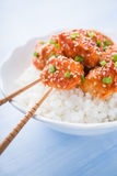 Spicy sweet and sour chicken with sesame and rice close up on blue background. Oriental food Royalty Free Stock Photography