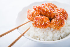 Spicy sweet and sour chicken with sesame and rice on white background close up. Oriental food Stock Images