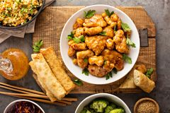 Spicy sweet and sour chicken with rice and cabbage. Spicy sweet and sour general tso chicken with fried rice and egg rolls overhead shot Royalty Free Stock Photo