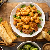 Spicy sweet and sour chicken with rice and cabbage. Spicy sweet and sour general tso chicken with fried rice and egg rolls overhead shot Stock Image