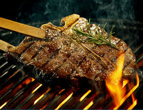 Spicy t-bone steak grilling over a summer barbecue. Spicy t-bone steak seasoned with rosemary grilling over a summer barbecue being turned with wooden tongs in a stock photography