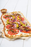 Spicy tarte flambee with pepperoni and olives Stock Image