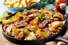 Spicy Tex-Mex beef entrecote steak with nachos. Oven baked with cheese served in an old cast iron skillet garnished with fresh coriander stock photo