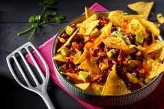Spicy Tex-Mex chili con carne with nachos. Au gratin garnished with fresh coriander in a high angle view with spatula on a dark background Stock Photography