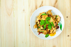 Spicy Thai basil chicken ready to eat on traditional plate with wooden spoon. Top View. (Shallow aperture intended for the aesthetic quality of the blur stock images