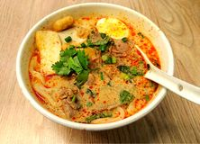 Thai Beef noodles. Spicy Thai Beef crossover Udon noodles with fish slices, half egg and Corianders royalty free stock images
