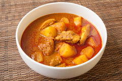 Spicy Thai red chicken curry. Called Massaman curry, in white bowl sitting on bamboo mat royalty free stock photography
