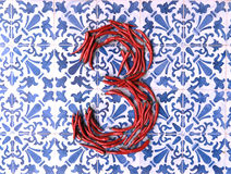 Spicy three on a tiled surface. 3D rendering of number three formed by chili peppers on a blue and white tiled background Stock Photography