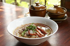 Spicy TOM YAM noodle soup with pork, lemongrass, chili pasted and lime juice Stock Photo