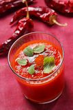 Spicy tomato soup. In glass with mint leaves and ground paprika Stock Photo