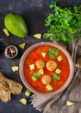 Spicy tomato soup with meatballs and vegetables. Served with avocado and parsley. Healthy dinner. Flat lay. Top view royalty free stock photos