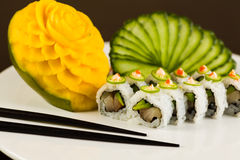 Spicy Tuna Roll. Fancy spicy tuna sushi roll with avocado and jalapeno pepper on a white plate garnished with sliced cucumber and carved mango fruit Royalty Free Stock Photos