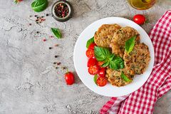 Spicy vegan burgers with rice, chickpeas and herbs. Salad tomato and basil. Vegetarian food. Top view. Flat lay royalty free stock photography