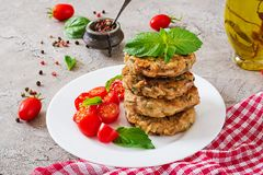 Spicy vegan burgers with rice, chickpeas and herbs. Salad tomato and basil. Vegetarian food stock images