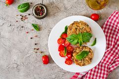 Spicy vegan burgers with rice, chickpeas and herbs. Salad tomato and basil. Vegetarian food. Top view. Flat lay stock photo