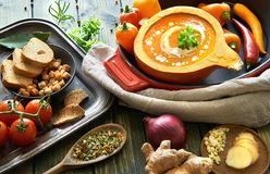 Spicy vegetable cream soup seasoned with chili, ginger and garli. C. Served in a hollowed pumpkin with cream and parsley. Autumn food background, text space Stock Photos