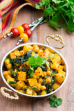 Spicy vegetable stew with curry and spinach. In a copper bowl on a wooden background Royalty Free Stock Photography