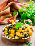 Spicy vegetable stew with curry and spinach. In a copper bowl on a wooden background Stock Image