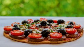 Spicy vegetarian pizza with cherry tomatoes, mushrooms, black olives and herbs on the gray kitchen table. Pizza background. With copy space on the green blurred Stock Photos