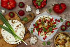 Spicy veggies tacos with roasted cauliflower, zucchini and tomato salsa on rustic wooden cutting board. Preparing healthy lunch vegetarian snack. Top view stock image