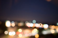 Spider backlit by a bokeh of city lights. Spider backlit by a colorful glow and bokeh of city lights shining in the darkness viewed as a silhouette Stock Photography