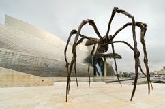 Spider. Bilbao. BILBAO - JULY 2: The photo shows the sculpture of a giant spider in the foreground and the Guggenheim Museum in the background. In the picture Royalty Free Stock Photo