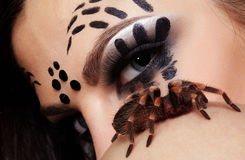 Spider-girl with spider Brachypelma smithi. Portrait of girl with spider bodyart of face  posing with real spider Brachypelma smithi on her shoulder Royalty Free Stock Photos