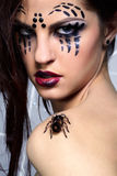 Spider-girl with spider Brachypelma smithi. Portrait of girl with spider bodyart of face zone posing with real spider Brachypelma smithi on her shoulder Royalty Free Stock Images