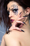 Spider-girl and spider Brachypelma smithi. Portrait of girl with spider bodyart of face zone posing with real spider Brachypelma smithi on her shoulder Stock Photo