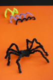 Spider for Halloween craft, black on orange. Black spider made of pipe cleaners on orange background. Halloween decoration, craft and fun concept royalty free stock photos
