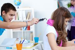 Spider play. Evil lad holding black spider while going to frighten his classmate at lesson royalty free stock images
