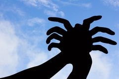 Spider shape hand silhouette in blue sky and cloud. Royalty Free Stock Photography