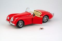 Spider stepping down from car toy. Spider stepping down from red convertible car toy royalty free stock photo