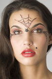 Spider web. Close up of young and nice brunette with spider web painted on face Royalty Free Stock Photo