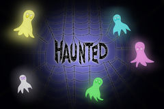 Spider web with glowing word haunted hanging in the middle Stock Photos