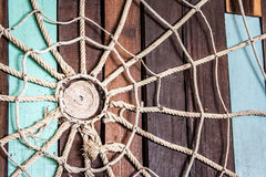 Spider web made of rope on the wood wall Stock Image