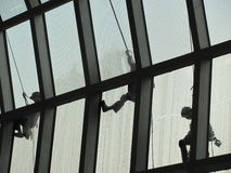 Spidermen, Bangkok. Cleaners or rather climbers are tethered to ropes as they clean the façade of the airport at Bangkok Stock Photo