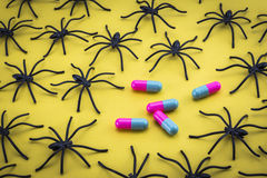 Spiders around capsules on yellow background, concept phobia to Stock Photos