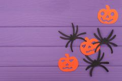 The spiders and pumpkins halloween silhouettes cut out of paper. On purple wooden board. Halloween holiday vector illustration