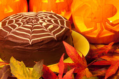 Spiders web chocolate cake and pumpkins Royalty Free Stock Image