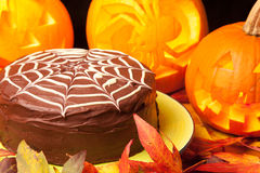 Spiders web chocolate cake and pumpkins Royalty Free Stock Photos