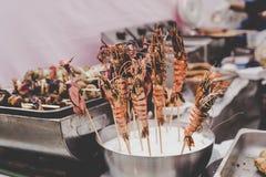 Spiedi arrostiti del calamaro e del gamberetto al mercato dell'alimento della via, fuoco selettivo Fotografie Stock