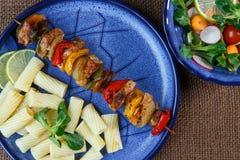 Spiedi arrostiti della carne con pasta sul piatto con sal di verdure Fotografia Stock