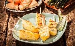 Spiedi dei cunei arrostiti dell'ananas sul piatto verde Immagini Stock