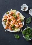 Spiedi di color salmone, olive, spinaci - spuntino, aperitivi, tapas Spiedo di color salmone arrostito del pesce su un fondo scur immagini stock libere da diritti